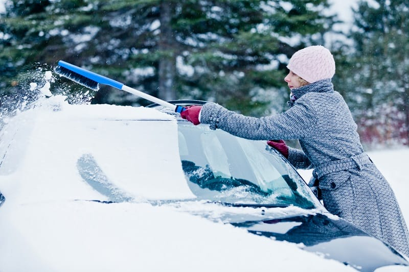 Woman Removing Snow from a Car with a Broom after the snow storm